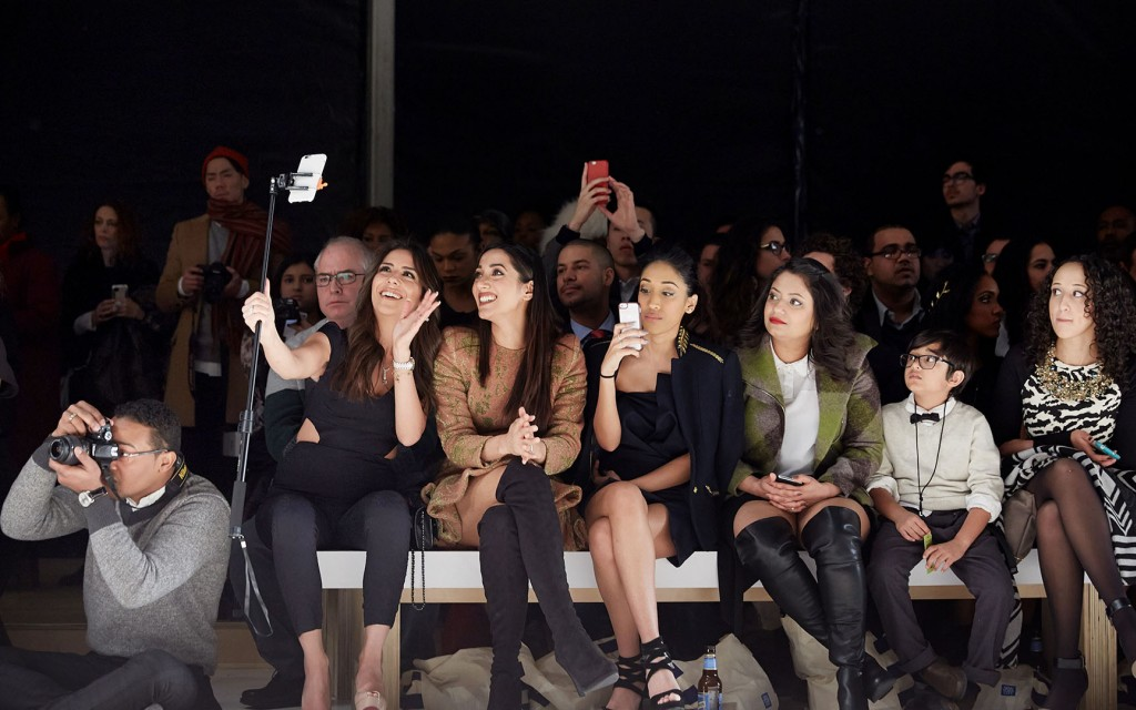 Front row vistors at a fashion show take selfies of each other.