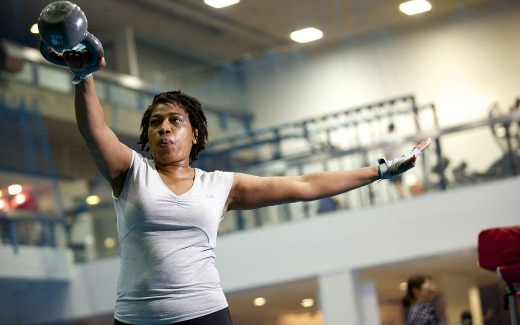 Gym member using kettlebells on the main sports hall floor